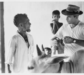 Peace Corps volunteer explaining inoculation of cows, East Pakistan, by Charles Harbutt/Magnum Photos, 1962