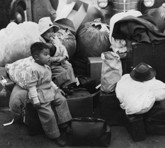 Japanese Americans waiting for a train to take them to Owens Valley, California, photograph by Russell Lee, April 1942