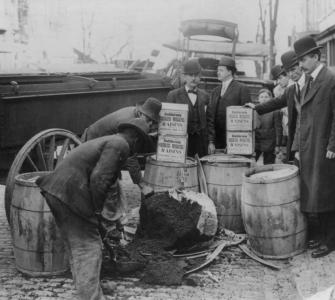 U.S. Marshal destroying worm-infested currants and raisins seized in Washington, D.C., bakeries, photograph, November 20, 1909