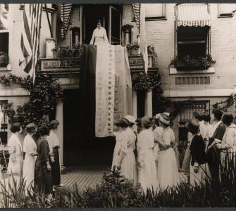 Suffrage Leader Alice Paul Standing above Ratification Banner