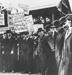 New York clothing workers carried signs in several languages demanding a closed shop and an eight-hour day.