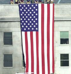 Following the terrorist plane attack on September 11, 2001, firefighters hoisted the American flag over the Pentagon.